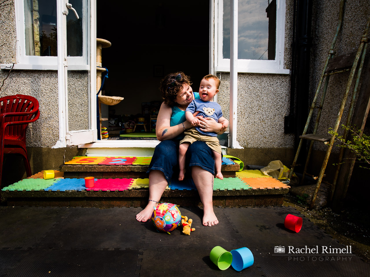 mother and son with downs syndrome sit on back step documentary portrait