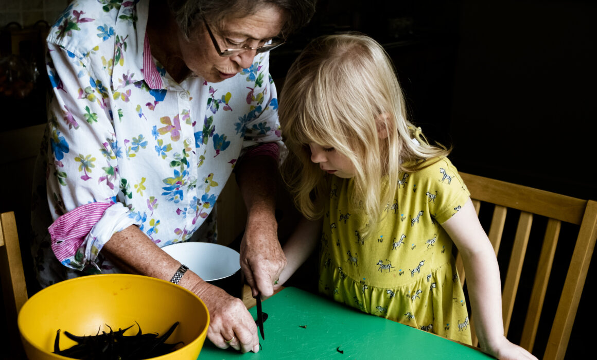 Grandmother and granddaughter chopping beans in the kitchen together day in the life photographer