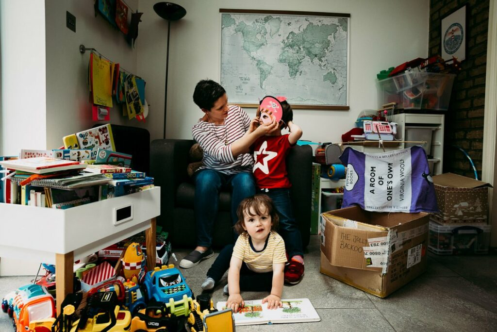 Mother in a striped top and jeans adjusts her son's pirate mask while younger son reads on the floor wearing a yellow striped t-shirt. A box has been made into a pirate ship saying The Jolly Backhoo with a tea towel with slogan A Room of One's Own as a flag. Natural family photography in Lee