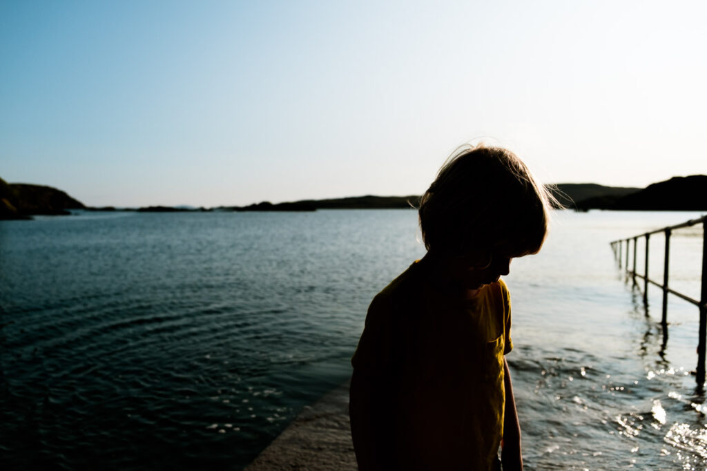 candid alternative portrait of boy in yellow t-shirt with profile in shade and the sea behind. UK vacation photography