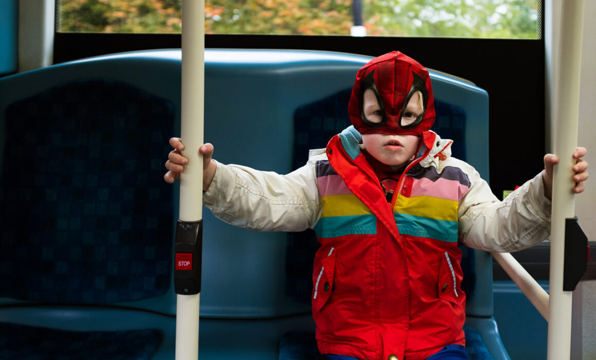 young boy with a spiderman facemask on and colourful winter jacket and a grumpy face on the London bus in a natural child portrait in London, UK