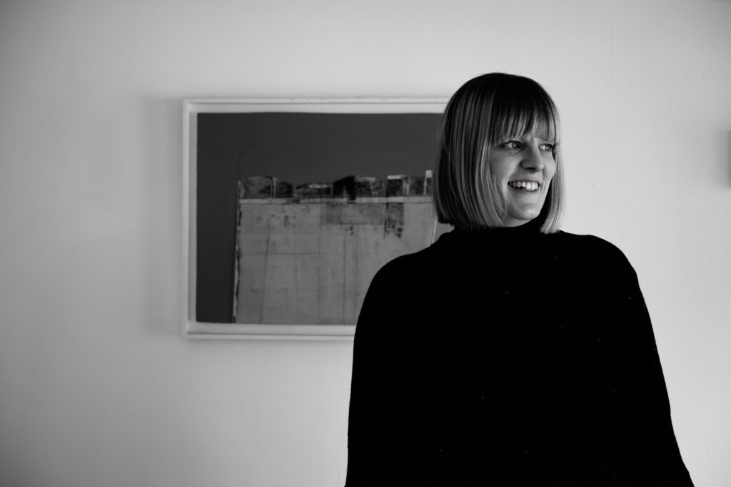 Natural light relaxed professional headshot of life coach Janine Green in black dress with painting in background, Crystal Palace, London