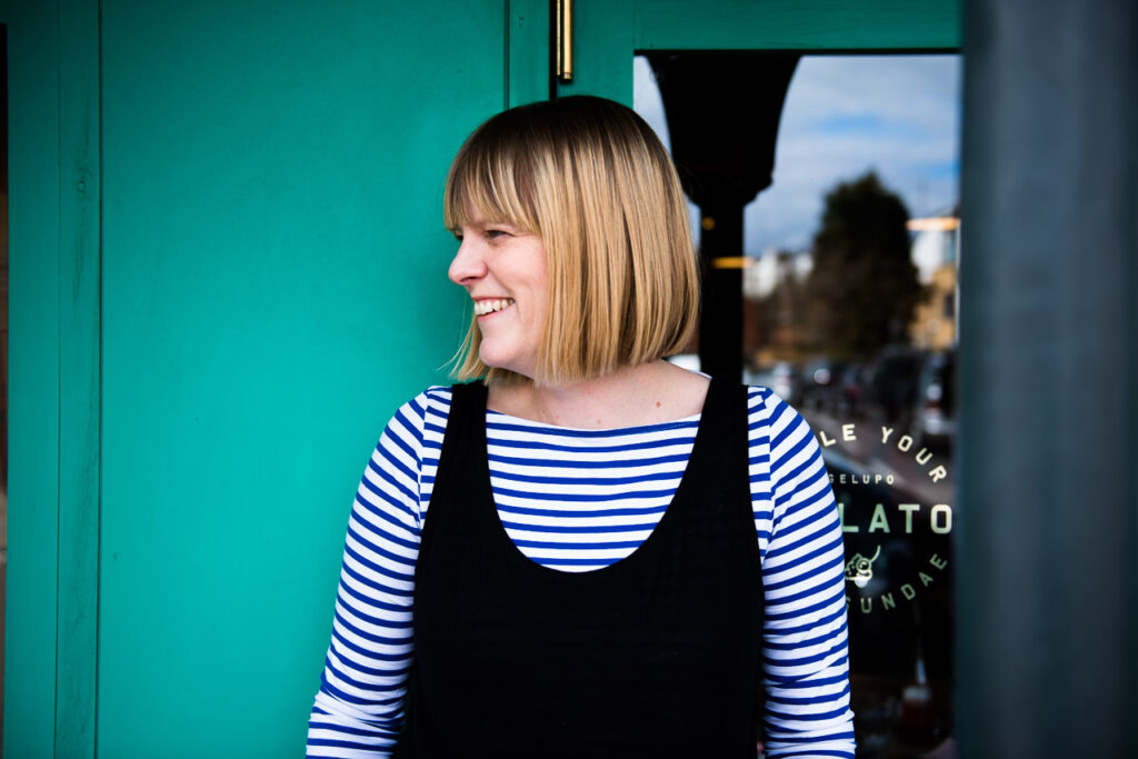 Fun and relaxed natural professional headshot of Janine Green in Crystal Palace with teal background, laughing