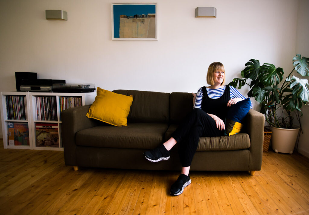 relaxed personal branding portrait of Janine Green Coaching on her sofa in her home with records and cheesplant in background, Crystal Palace, London