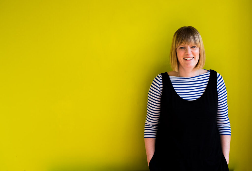 Natural headshot of Janine Green Coach against lime green background, London