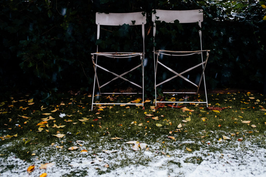 two white deck chairs in the snow with falling snow
