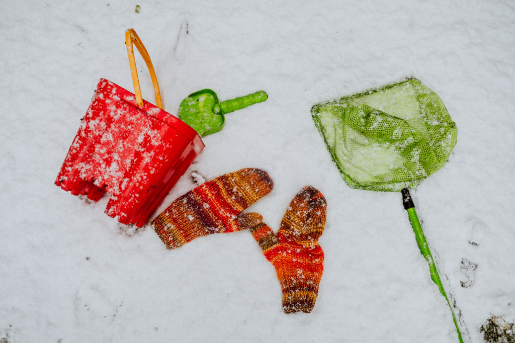 red child's bucket and green spade with green fishing net lying in the snow alongside a pair of orange woollen mittens