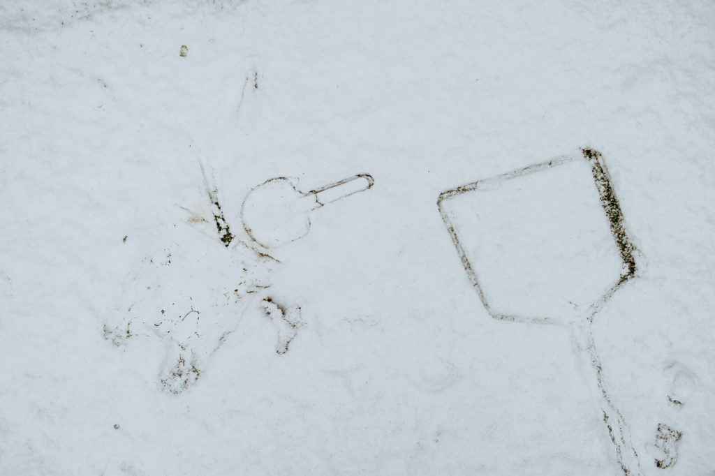 the imprint of a child's seaside bucket and spade and a fishing net in the snow