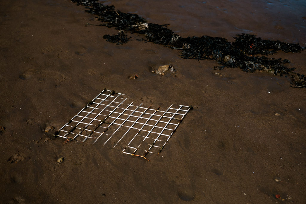 white metal grate lying on the sand on the strandline at Whitby harbour