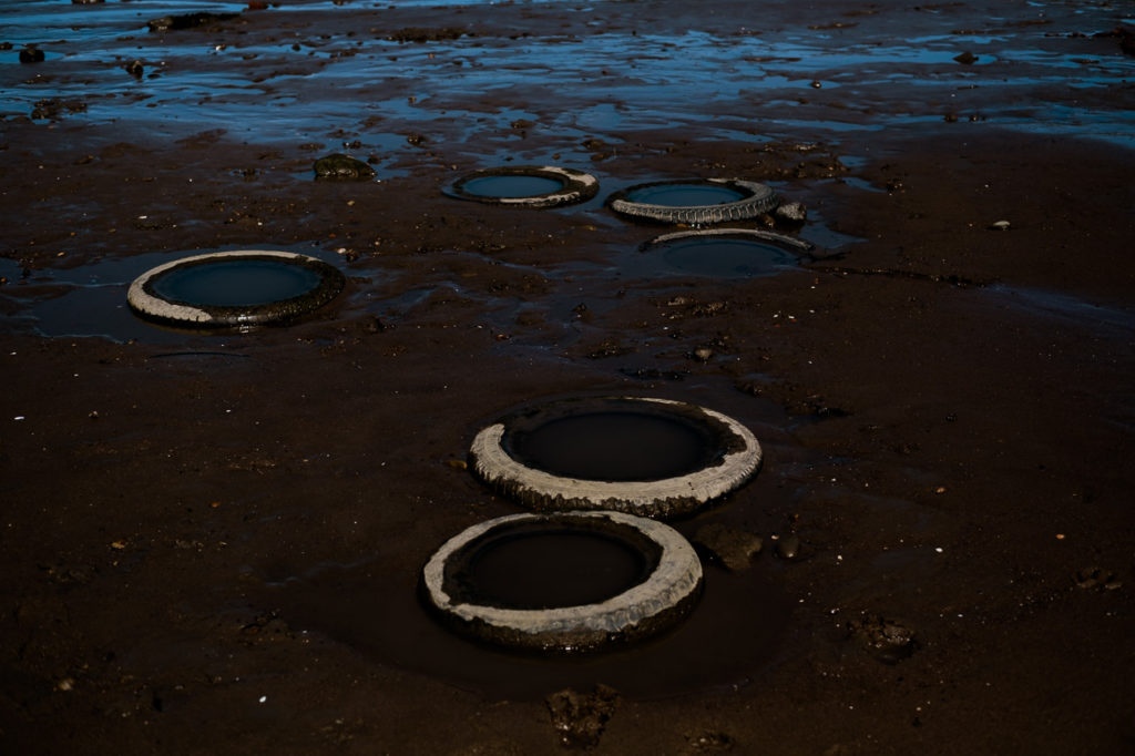 old tyres buried in the sand on the strandline at Whitby harbour