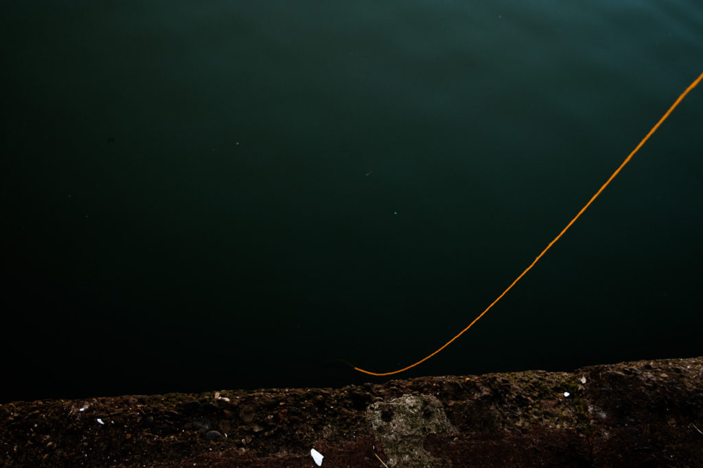 Orange fishing line descending into the sea at Whitby off the jetty