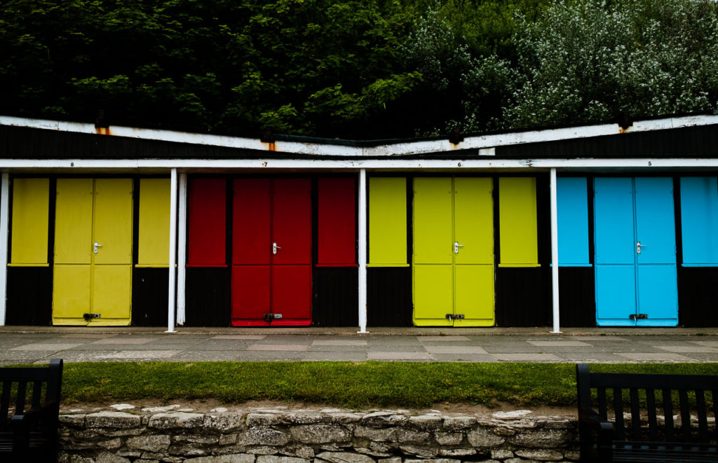 closed up beach huts in red, yellow and blue at Filey sea front North Yorkshire