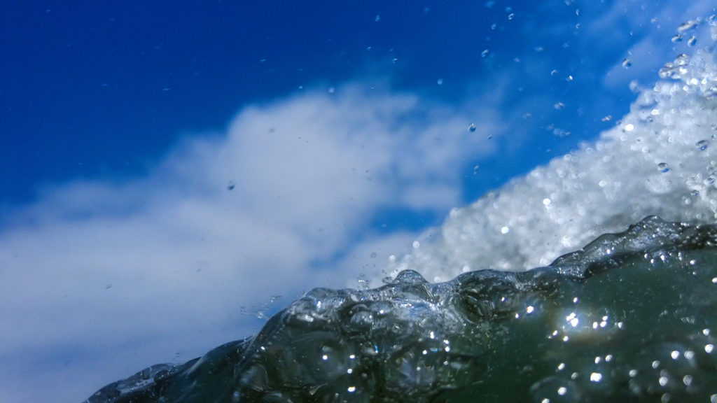 immersed water of a wave rolling over the camera