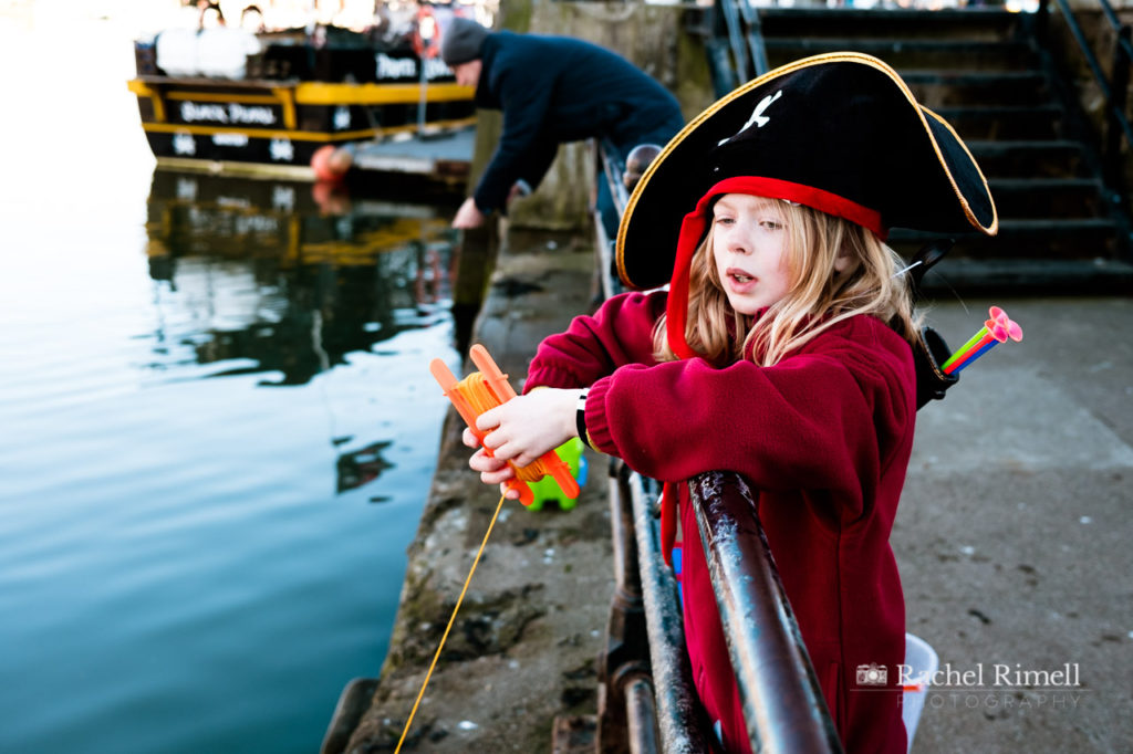 Girl dressed as a pirate crab catching off Whitby pier