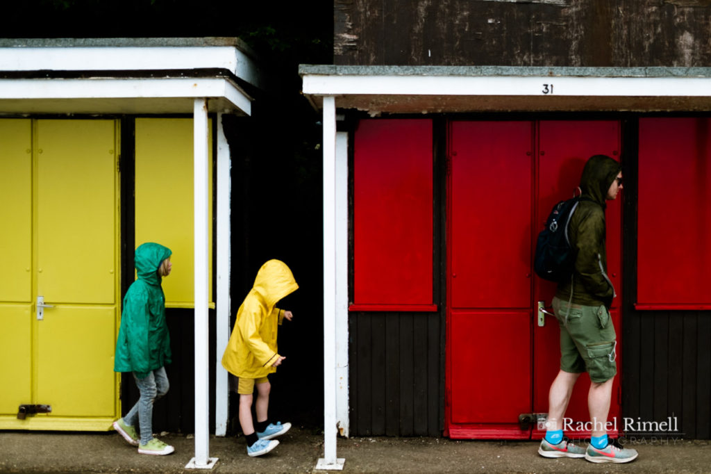 A dad with two children in the rain walking along the beach huts at Filey promenade wearing green and yellow raincoats